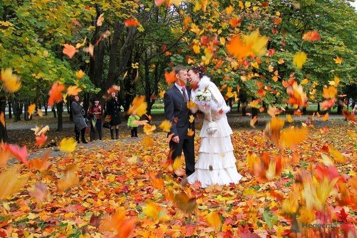 Жених и невеста стоят, прислонившись друг к другу, в осеннем парке
